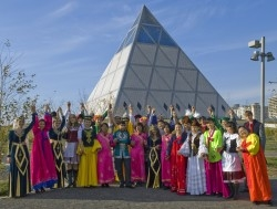 Representatives of different nationalities pose in front of the Pyramid of Peace in Astana, Kazakhstan. The Pyramid, constructed in 2006, represents country's spirit of tolerance and peace.