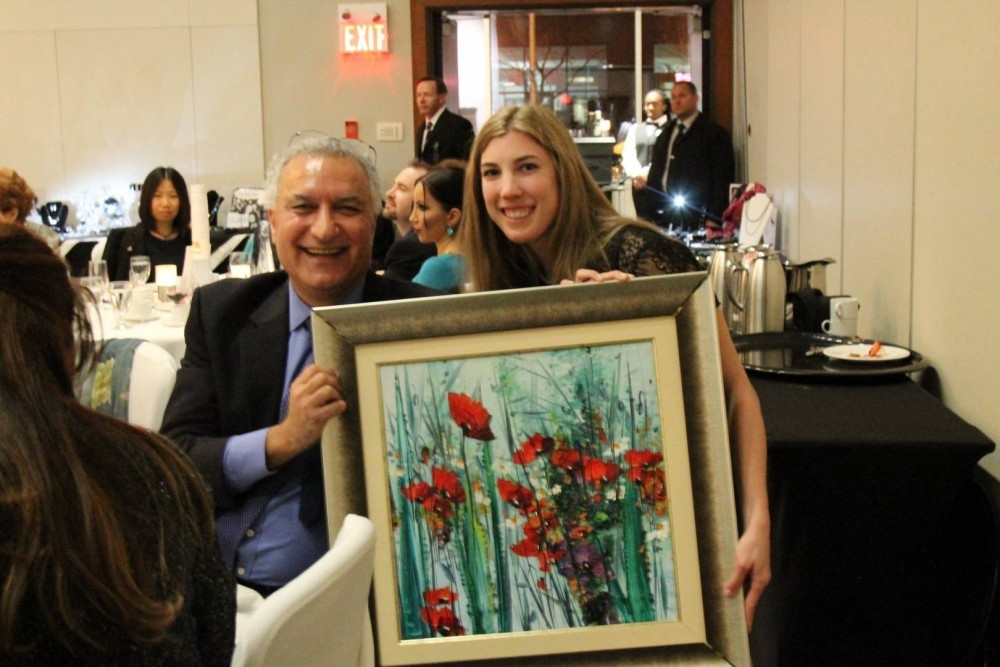 an Akkaya holding a painting by Hikmet Çetinkaya he bought at the auction.