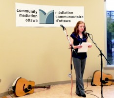 Coordinator/Coordinatrice, Meredith St. Denis, gives a speech about the services provided by Community Mediation Ottawa. Photo Courtesy of Alessandra Gerebizza